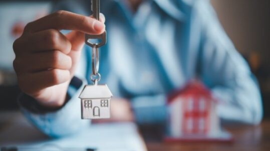 Real estate agent holding a house key in his hand