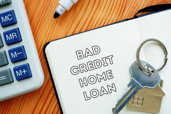 """House key, calculator and notebook with words """"bad credit home loan"""""""