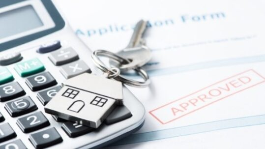 Approved mortgage application with house key and calculator